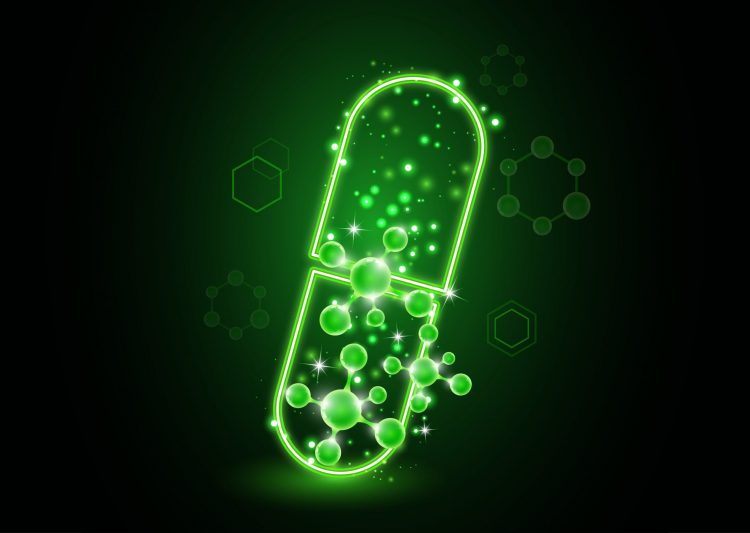 Glowing green pill with molecules coming out of it