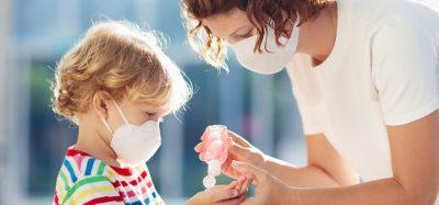 Mother handing child hand sanitiser